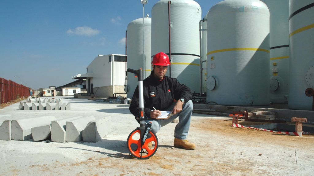 Man using a Measuring Wheel on a Construction Site
