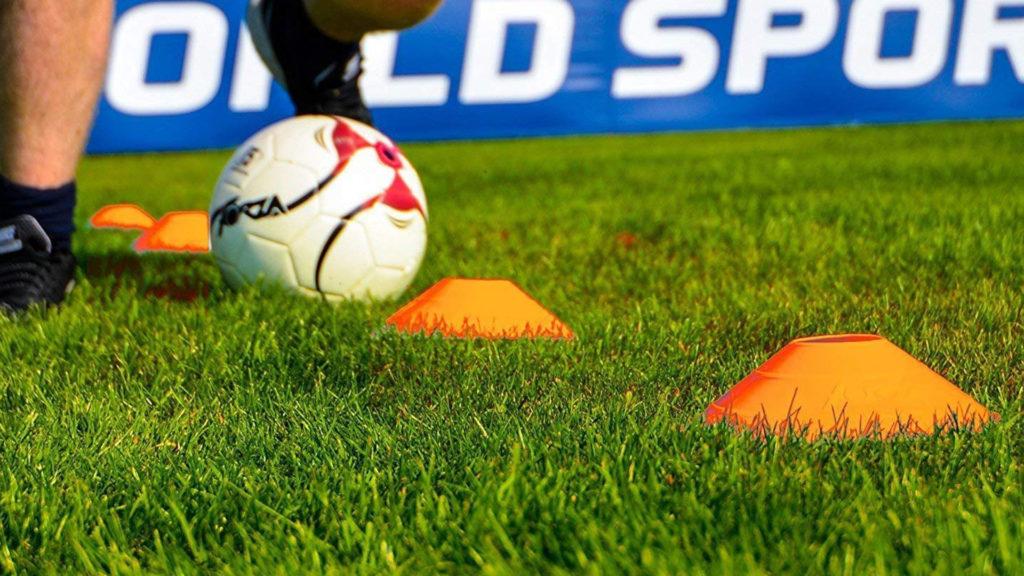 Dribbling a soccer ball through sports cones